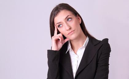 首をかしげるスーツ姿の白人女性の写真