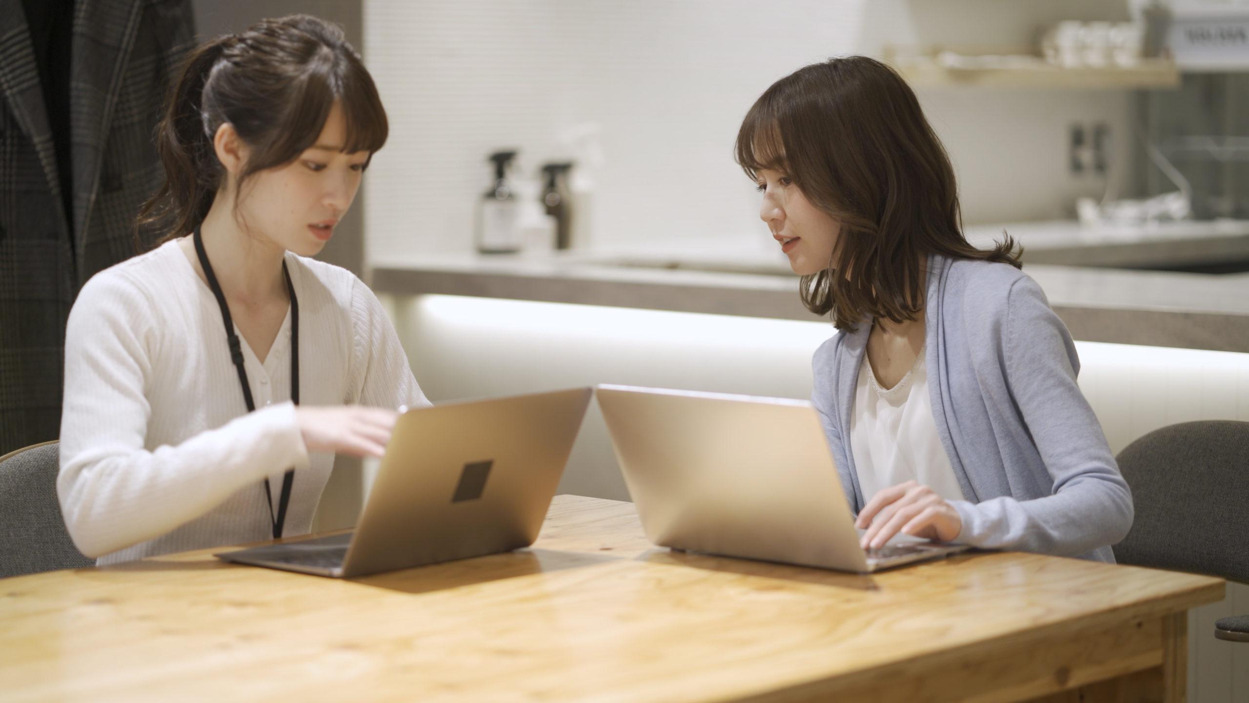 パソコン画面を前に話し込む女性の写真